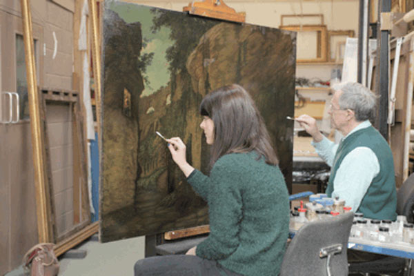 Conservators work on restoring one of Joseph Wright's Colosseum paintings. Courtesy of Derby Museums Trust.