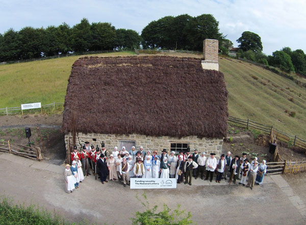 aerial shot of stone cottage with heather thatch with lots of people in 18th century dress