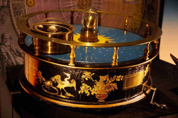 orrery circular object with brass handle to turn solar system and pictures of phoenixes painted on the side