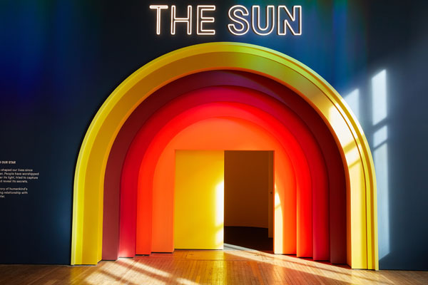 brightly painted yellow orange and red semicircular door to the sun exhibition
