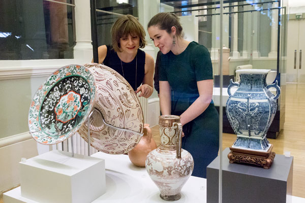 two women surrounded by large ornamental ceramics